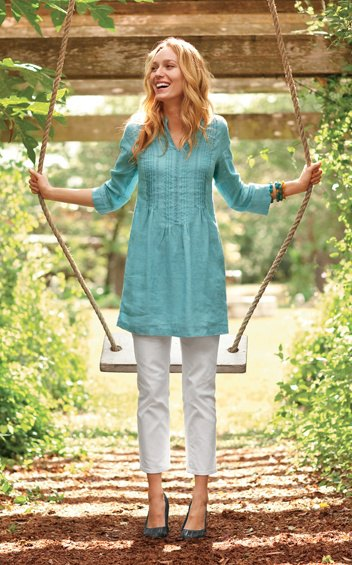 blue tunic top with three-quarter sleeves and gathered waist and white, cropped trousers