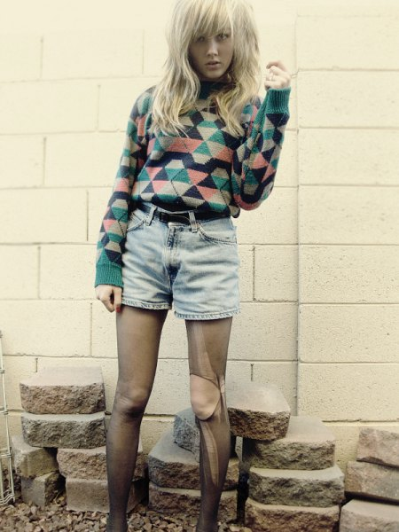 blushing and black diamond-printed sweater with high-waisted denim shorts with a belt
