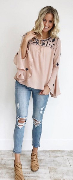 blushing and black blouse with wide ruffle sleeves and ripped and shortened jeans