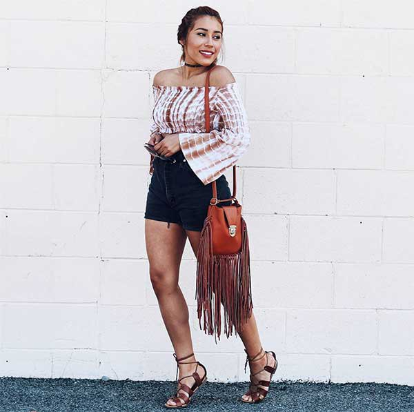 Blush and white ties stain the shoulder blouse with black mini-shorts