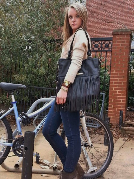 Blushing knitted sweater with blue skinny jeans and black leather bag