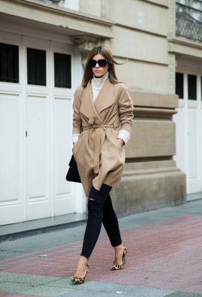 Blushing pink wool coat with a belt and black skinny jeans