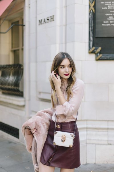 blushing pink blouse with black leather mini skirt