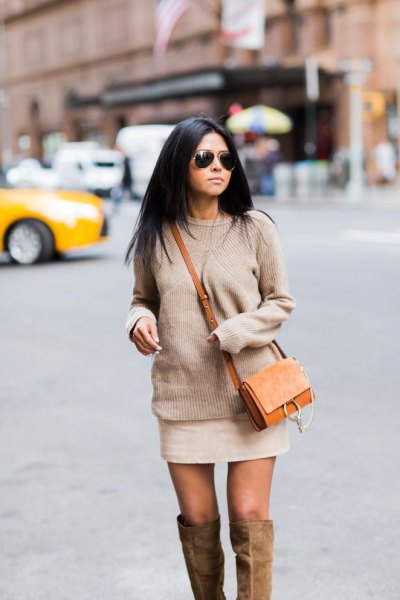 Blushing pink chunky knit sweater with mini ivory skirt and brown suede bag