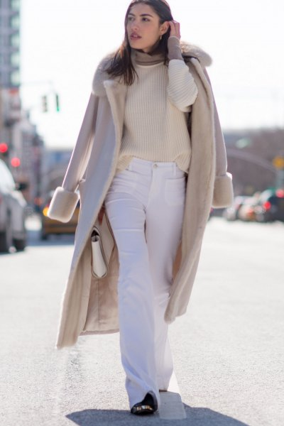 Blushing pink coat made of wool with a faux fur collar and flared white jeans