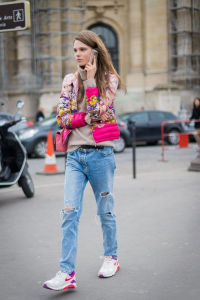 blushing pink floral print bomber jacket with boyfriend jeans and white trail shoes