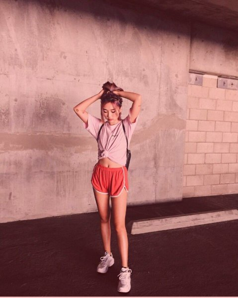 blush pink knotted t-shirt with red running shorts