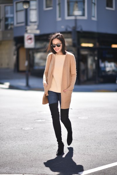 blush pink long jacket with blue high jeans and black thigh high boots