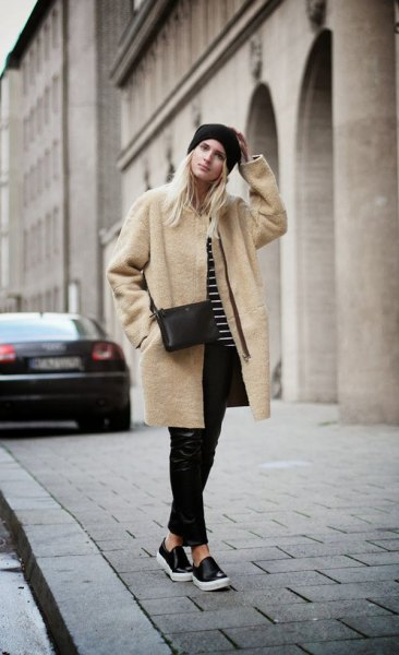 Blush pink long woolen coat with black leather pants and slip-on canvas shoes