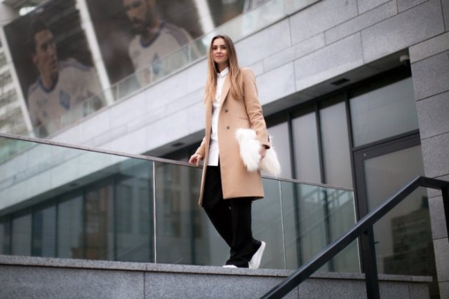 blushing pink longline wool coat with black trousers and white clutch handbag made of faux fur