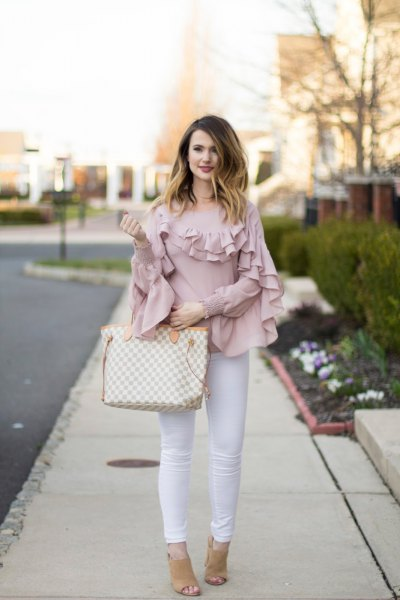 Blush pink ruffle sleeves and neck shirt with white skinny jeans