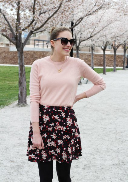 Blushing pink sweater with a black and white mini skirt with a floral pattern