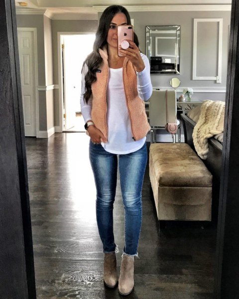 blushing pink waistcoat with a white long-sleeved T-shirt and narrow, fleece-lined jeans