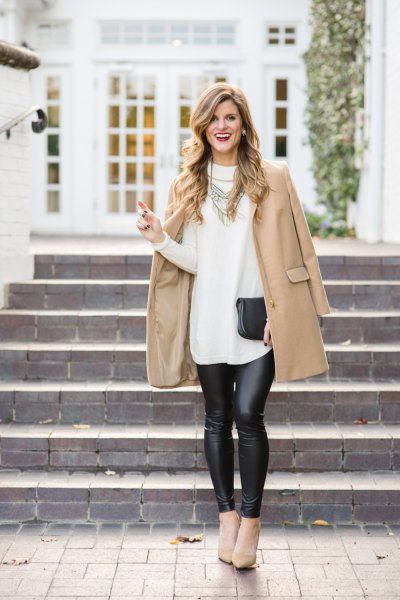 Blushing wool coat with a white long sweater and black leather leggings
