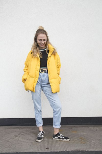 bright yellow jacket with a black, shortened sweater and light blue high-rise jeans