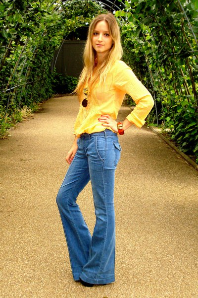 bright yellow long-sleeved blouse with blue flared jeans
