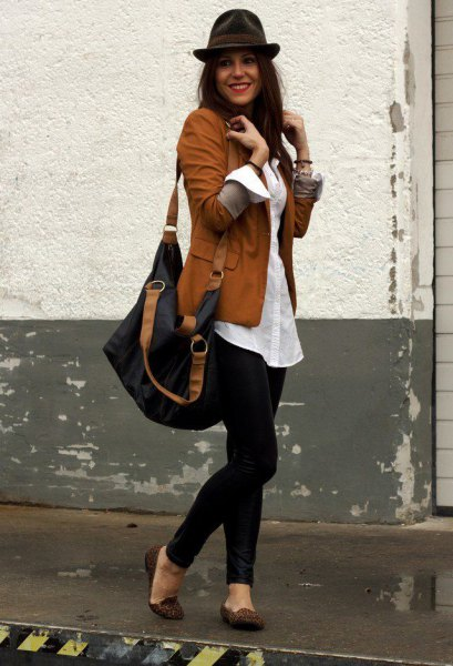 brown blazer with white, oversized shirt with buttons and black floppy hat