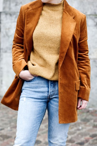 brown corduroy blazer with green sweater and light blue jeans