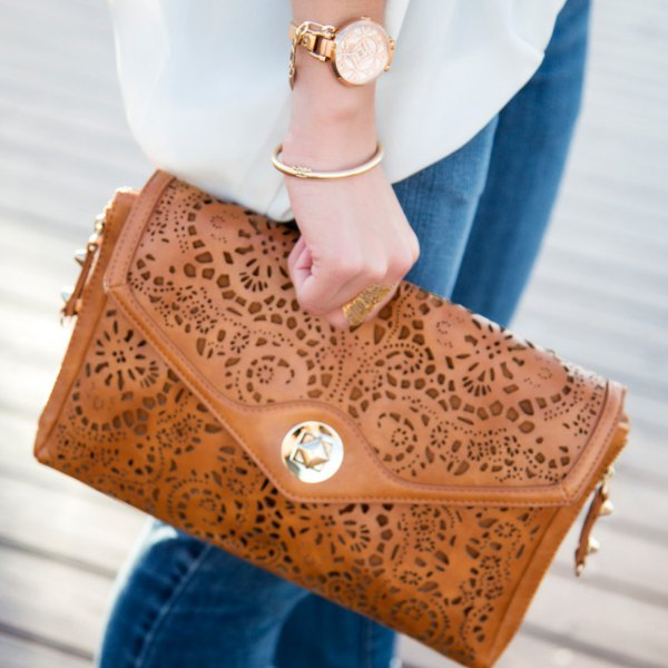 brown neckline clutch made of soft leather with white chiffon blouse and blue jeans
