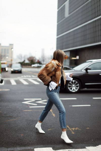 brown faux fur coat with gray skinny jeans