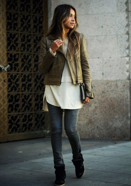 brown leather biker jacket with white tunic top and gray jeans