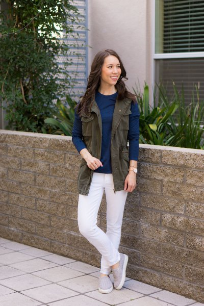brown utility vest with dark blue long-sleeved top and white jeans