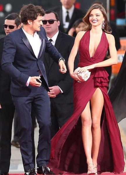 Burgundy-colored maxi wrap dress with deep V-neckline and golden strappy heels