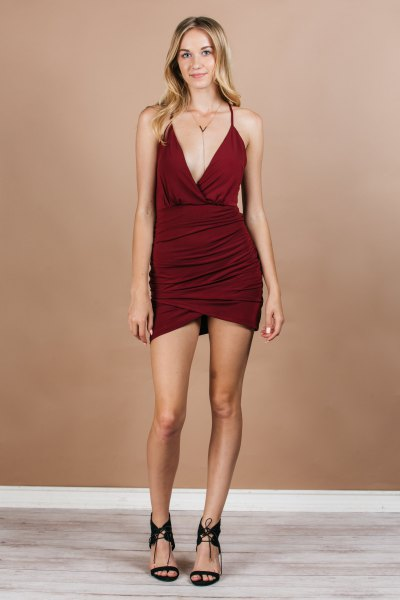 Burgundy-red, figure-hugging wrap dress with a deep V-neckline and open toe heels