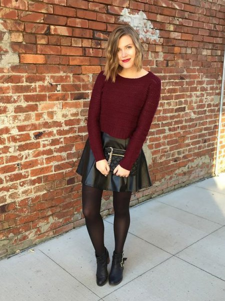 Burgundy-red, figure-hugging knitted sweater with black leather mini skirt and brown stockings