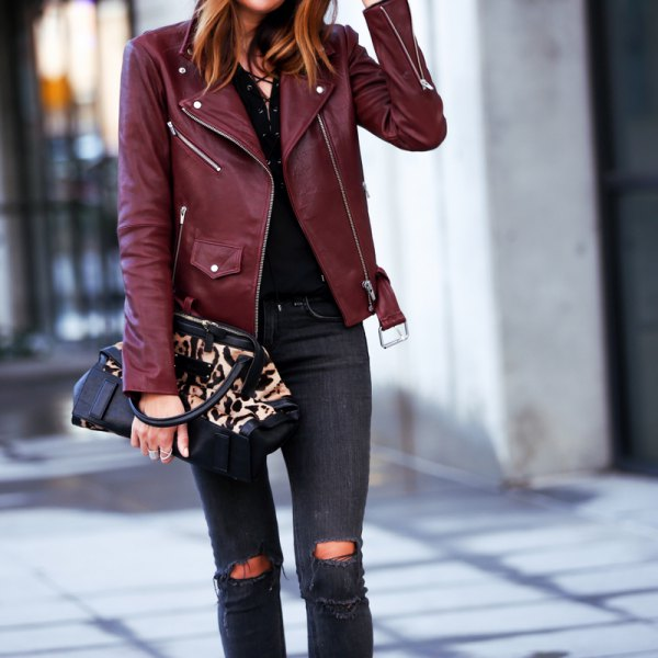 Burgundy leather jacket with black shirt and ripped skinny jeans