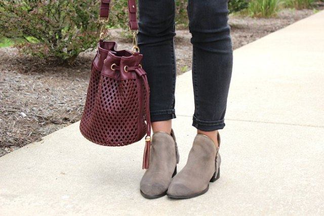 Burgundy red handbag made of soft leather with a white blouse and black, narrow-cut ankle jeans