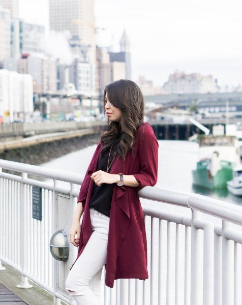 Burgundy trench coat with black sweater and white skinny jeans