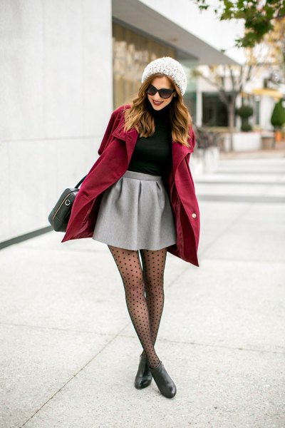 Burgundy wool coat with a light gray skater skirt and dotted stockings