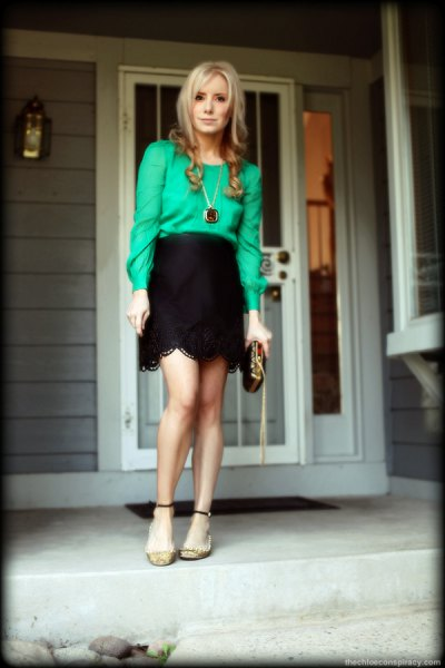Buttonless blouse with a black, high-waisted miniskirt with a scalloped edge
