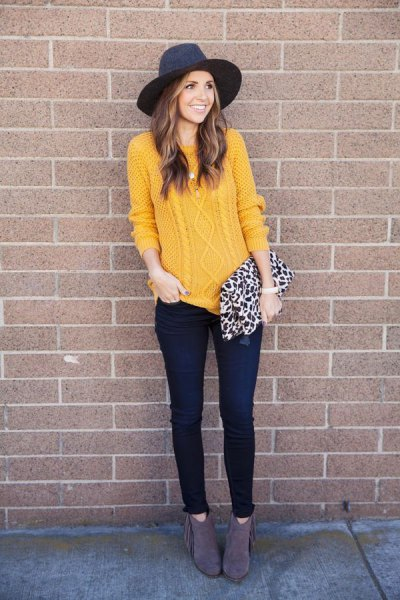 Cable knit mustard sweater with a black felt hat and wallet with a leopard print