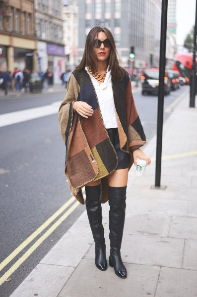 black wool coat in camel and black color with flat leather boots above the knee