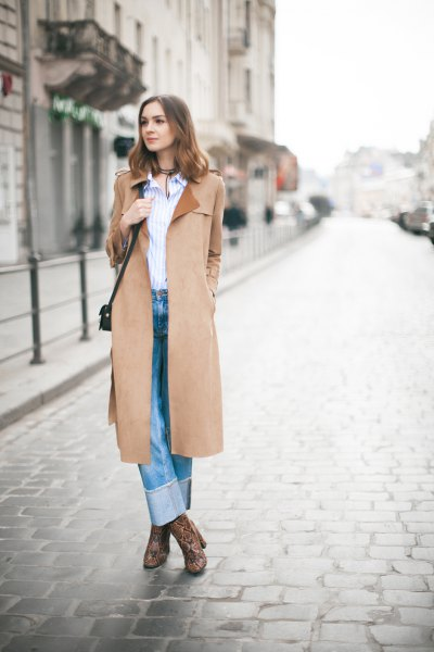Camel coat with a blue and white vertical striped shirt and cuffed jeans