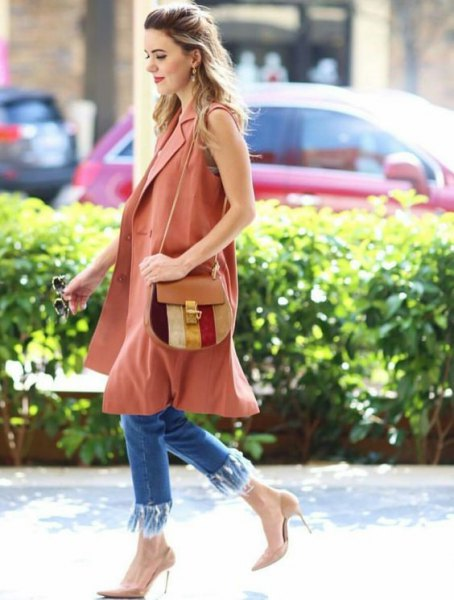 sleeveless camel coat with blue skinny jeans with fringes