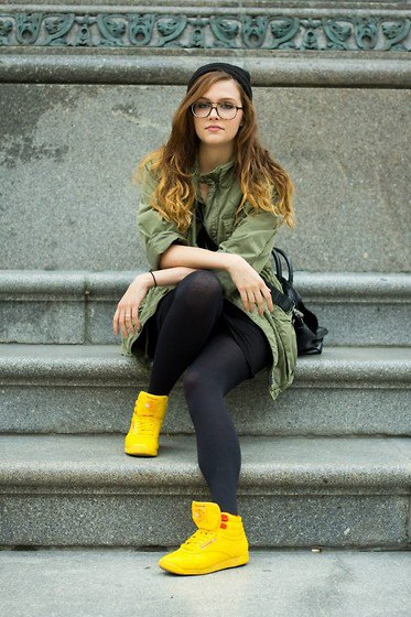 Camel trench coat with black stockings and yellow shoes