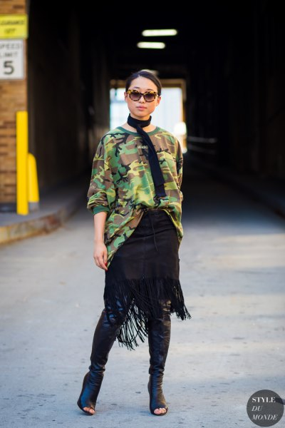 Oversized camo sweater with knee-high boots in black leather with an open toe