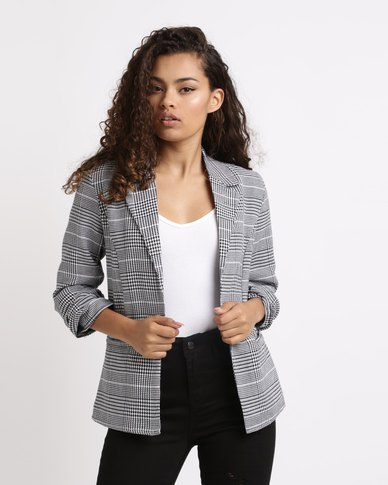 Checkered blazer with white tank top and black high-rise jeans