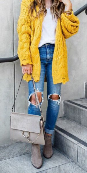 coarse cable knit cardigan with ripped blue jeans