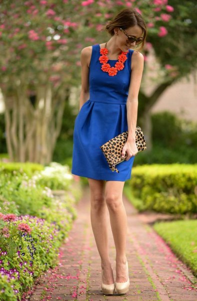 Cobalt blue sleeveless mini dress with a gathered waist and clutch with leopard print