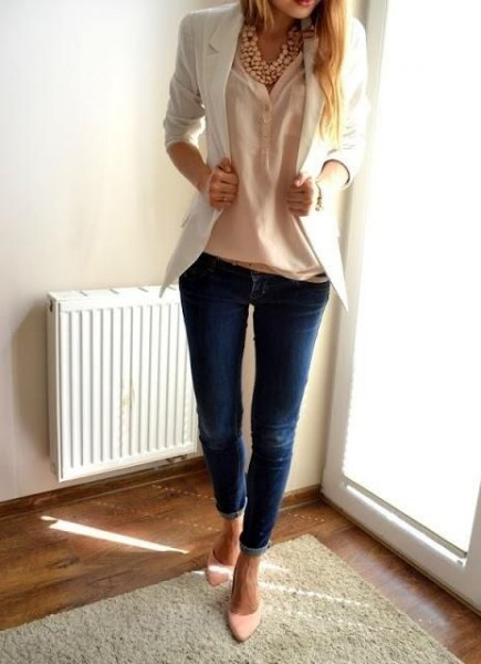 Cream-colored blouse with an ivory-colored blazer and dark blue skinny jeans