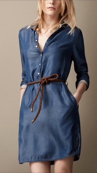 dark blue long sleeve tunic with button placket on the front and unwashed denim