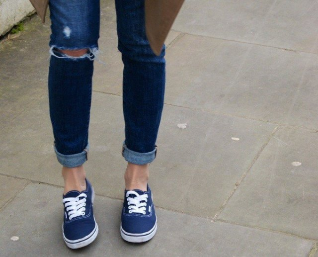 Dark blue skinny jeans with a brown parka jacket and dark blue sneakers