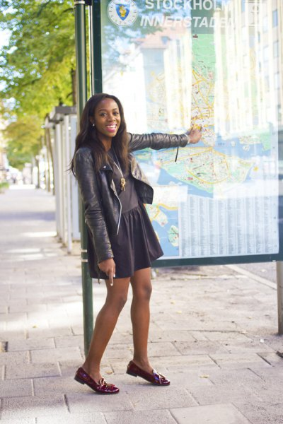 dark gray leather jacket with skater skirt and burgundy-colored slippers