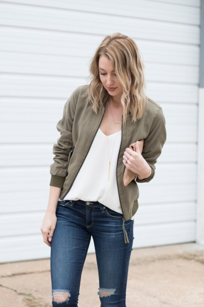 deep chiffon blouse with V-neckline, olive green jacket and ripped jeans