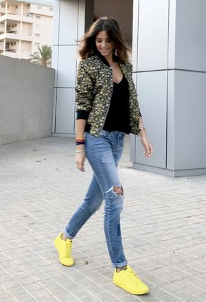 Bomber jacket with a floral pattern, black top with deep V-neck and yellow sneakers