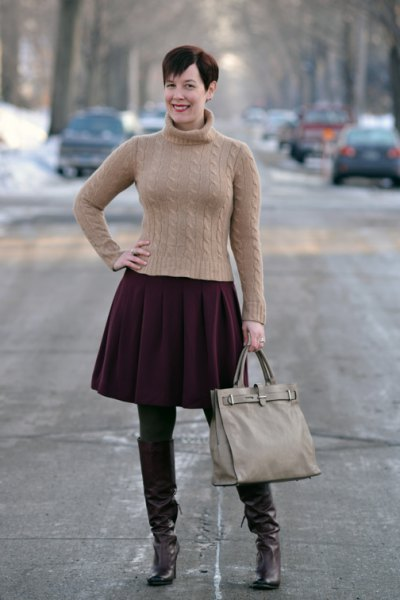 Figure-hugging green turtleneck with a black pleated skirt and brown tights